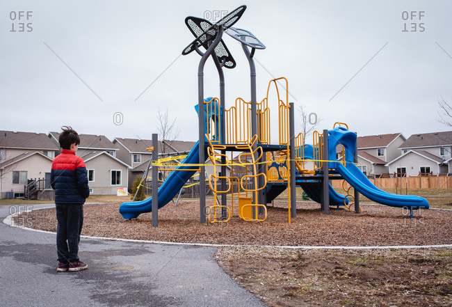 Young boy looking at closed playground during Covid 19 pandemic.