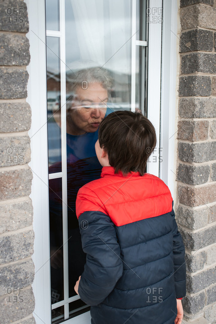 Young boy looking through window at grandma during Covid 19 pandemic.