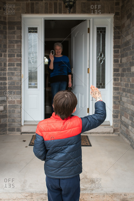 Social distance visit between young boy and his grandmother at home.