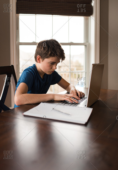 Tween boy working on his homework on a laptop commuter at home.
