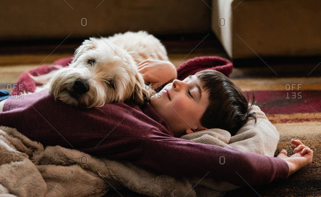 Boy and his dog cuddling on the floor together on a blanket.