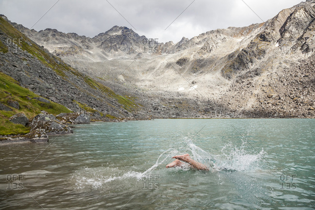 Man dives in for swim in Upper Reed Lake, Talkeetna Mountains, Alaska