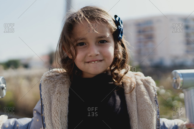 Portrait of a four-year-old girl smiling in a park by day