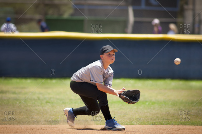 Little League infielder about to catch a baseball