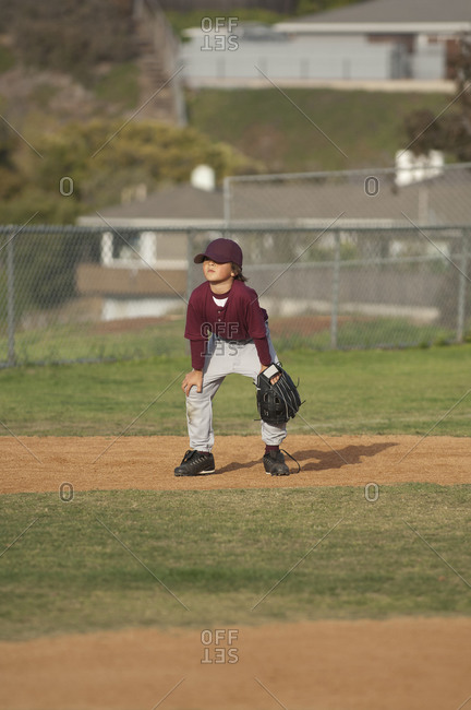 Little League baseball boy in ready position in the infield
