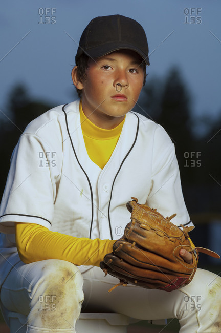 Portrait of a boy in white baseball uniform with his glove