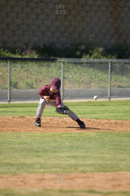 Little League baseball boy missing a ground ball on the infield