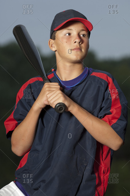 Portrait of a baseball player holding his bat wearing a warm up jacket