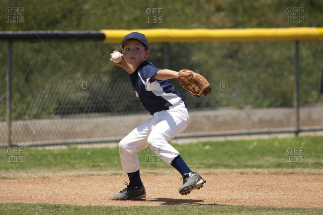 Little League baseball infielder ready to throw to first base