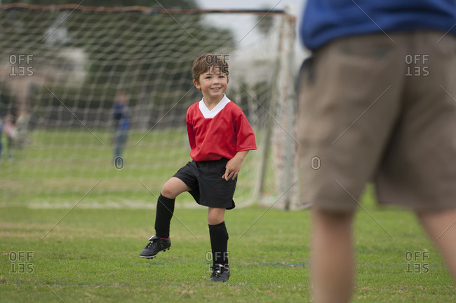 Young boy with big smile on a soccer field
