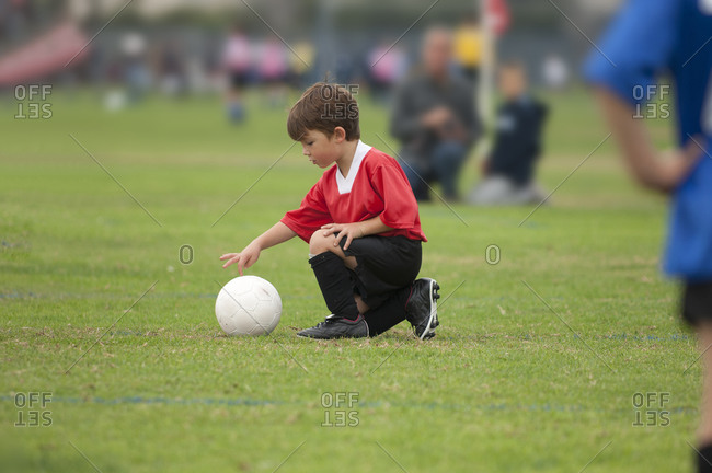 Young boy touching a soccer ball with his finger on a soccer field