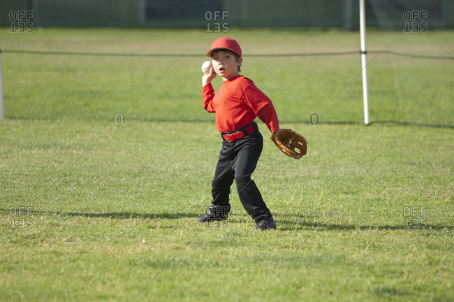 Young boy throwing a baseball on the TBall field
