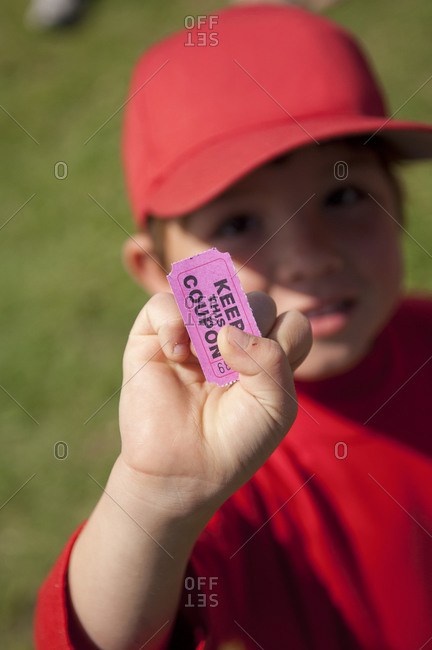 Young boy holding his coupon for the snack shack after his little league game