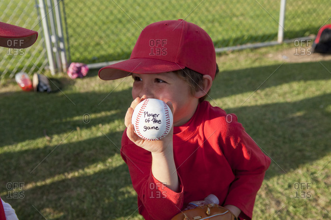 Young boy holding his player of the game baseball on the TBall field