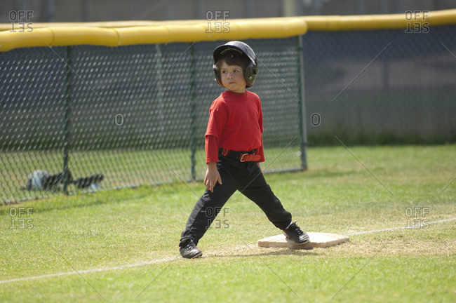 Young boy smirking on third base on the TBall field