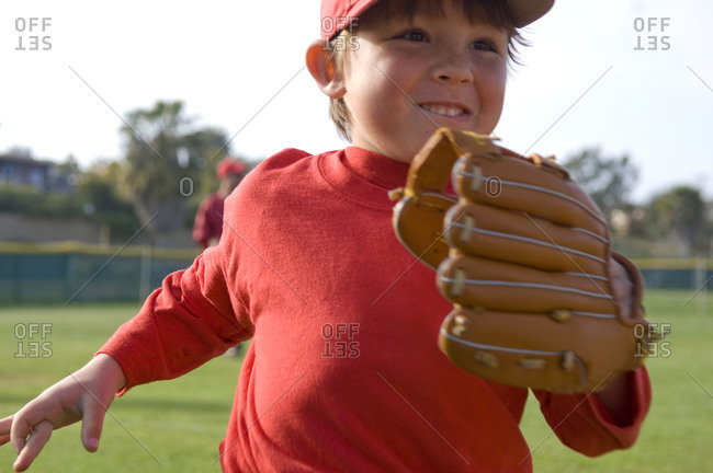 Close up of young boy running off the TBall fiels with a big smile