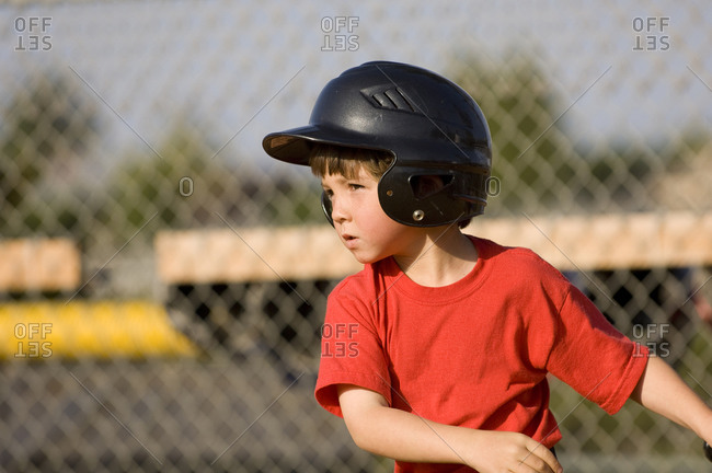 Young boy in baseball helmet concentrating on his hit