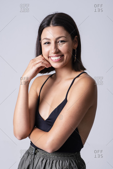 Beautiful young girl posing and smiling in a studio with a grey