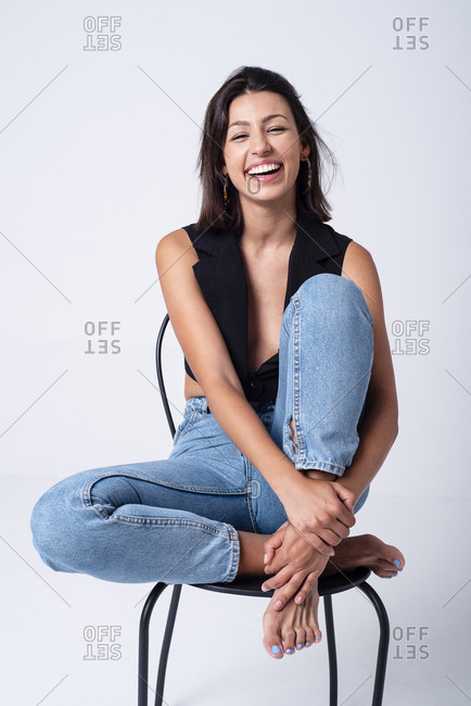 Beautiful young girl sitting on a chair, having fun posing in a