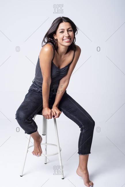 Pretty young girl sitting on a stool, having fun posing in a stu