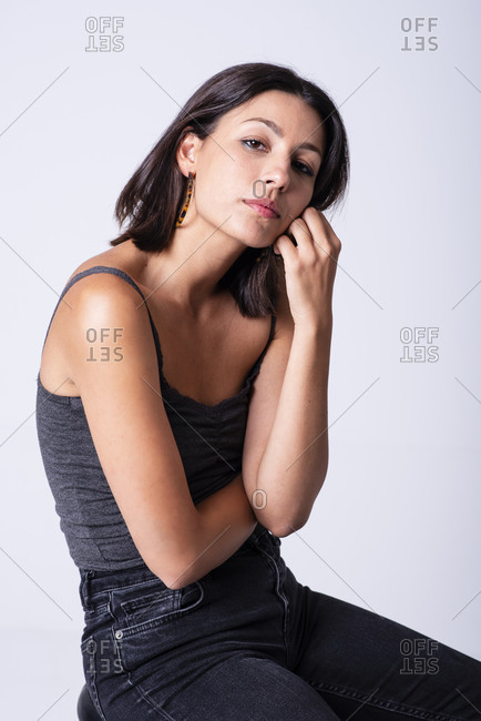 Pretty girl posing in a studio with a grey backdrop