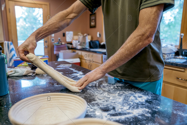 Man stretching sourdough bread dough in messy kitchen