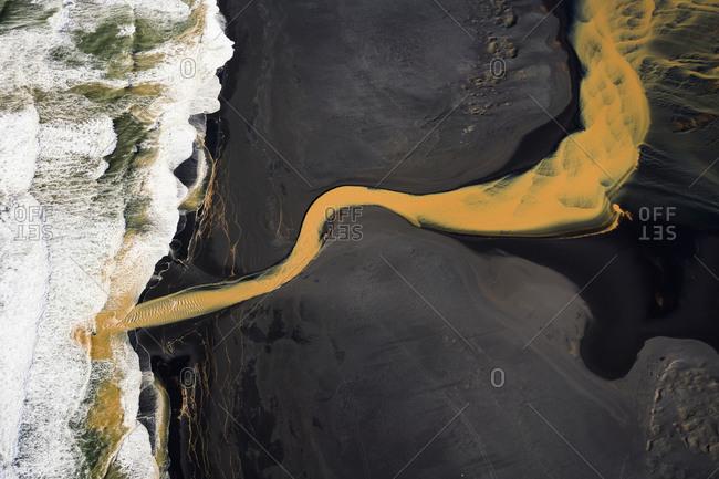 Aerial view of braided orange river flowing into ocean in soothe