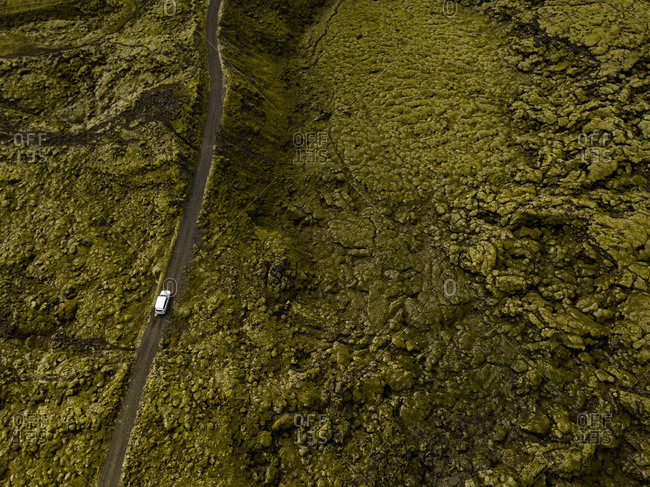 Aerial view of car driving through moss covered lava rocks in Ic