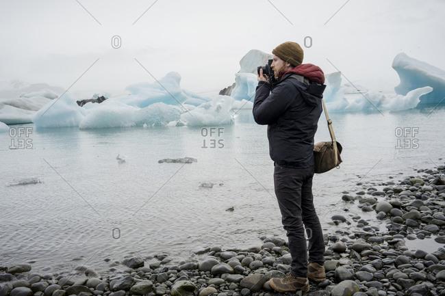 Man taking a photo at Jokulsarlon glacier lagoon at dusk
