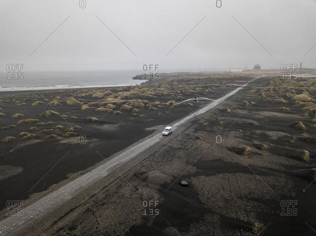 Aerial of car driving down sandy gravel road near Stokksnes, Ice