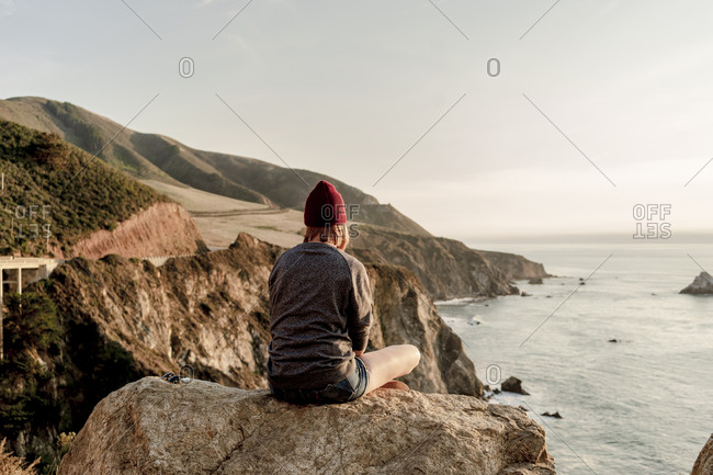 Woman sitting on rock overlooking Big Sur coastline