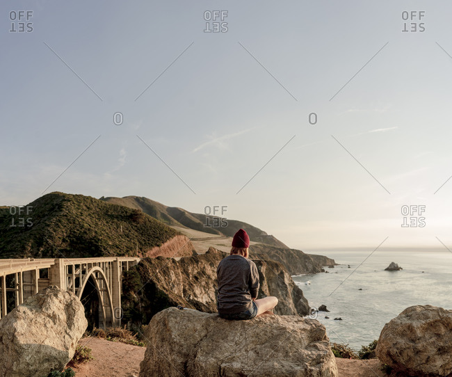 Woman sitting on rock overlooking Big Sur coastline and Bixby Br