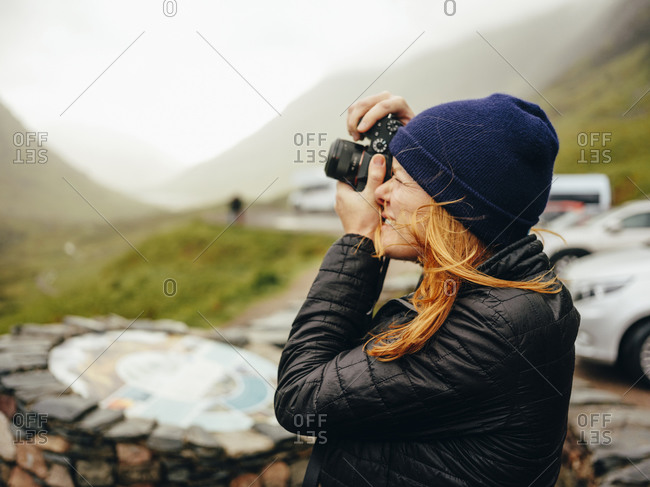 Woman photographing Three Sisters Of Glencoe, on a wet day