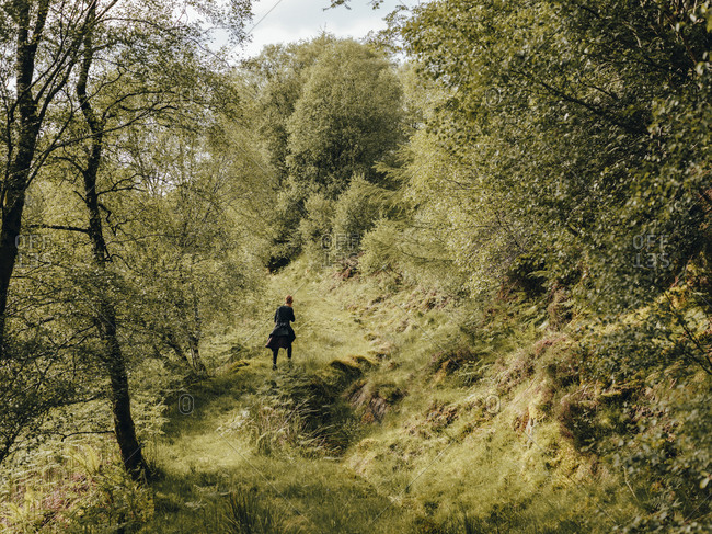Woman hiking up grassy trail in Scotland forest