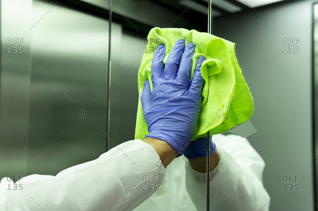 coronavirus. Worker disinfecting hospital elevator to avoid contagion.