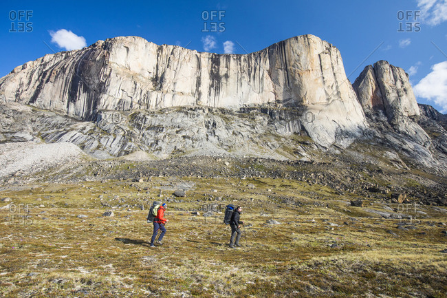 Two backpackers traverse below Baffin Island mountains.