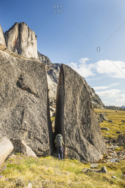 Backpacker squeezes through gap in cracked erratic boulder