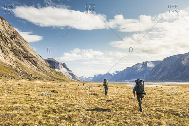 Two mountaineers cross arctic tundra in Akshayuk Pass.