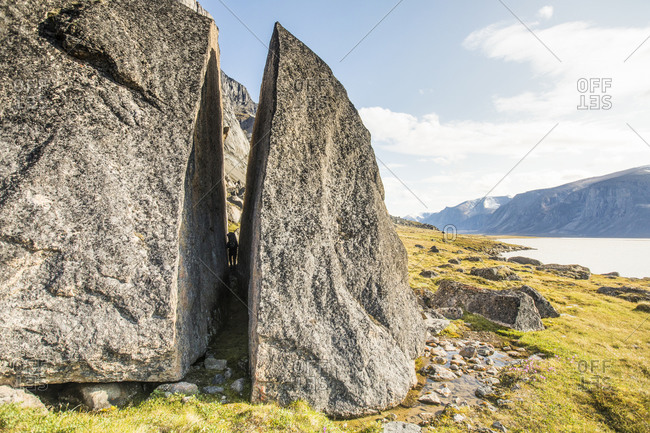 Backpacker squeezes through cracked erratic rock in the arctic.