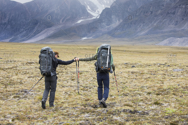 Two backpackers (friends) fist bump during journey across arctic pass