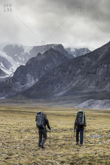 Rear view of two backpackers heading into the mountains.