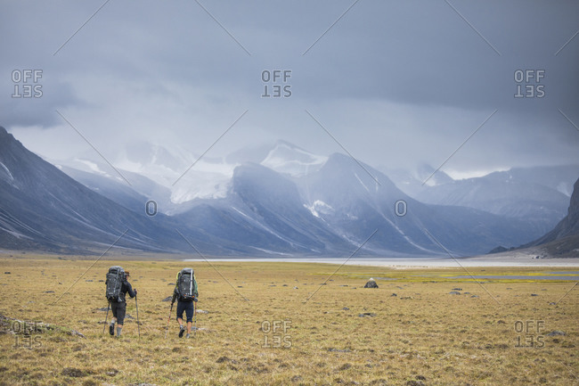 Rear view of two backpackers hiking through open valley in the arctic.