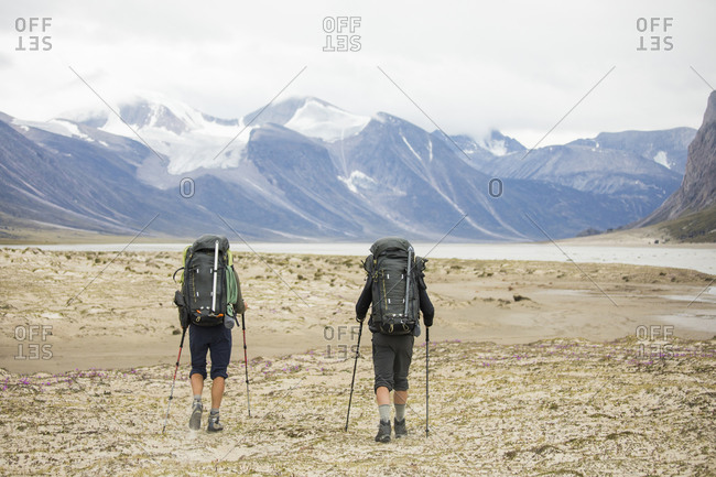 Two backpackers hiking in Auyuittuq National Park, Canada.