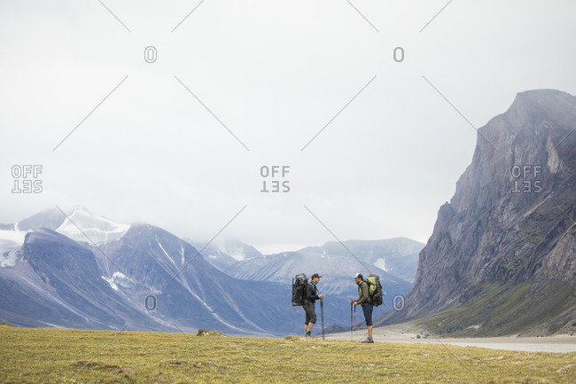 Two friends stop and discuss route during backpacking trip.