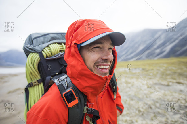 Portrait of happy backpacker with red rain jacket on.