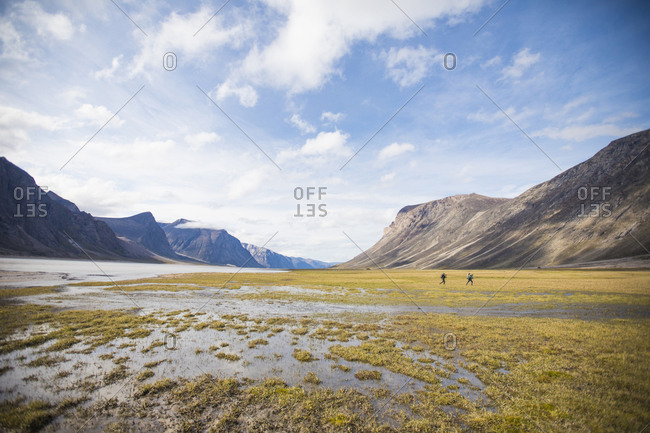 Two backpackers cross wet tundra in Akshayak Pass.