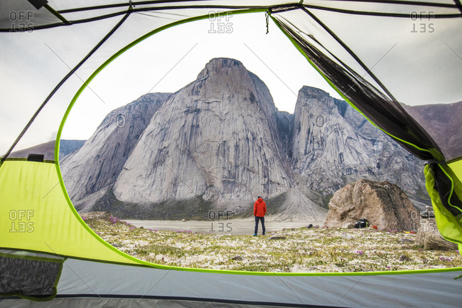 View of climber and mountain through open tent door.