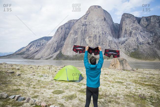 Man hanging underwear on clothesline during climbing trip.