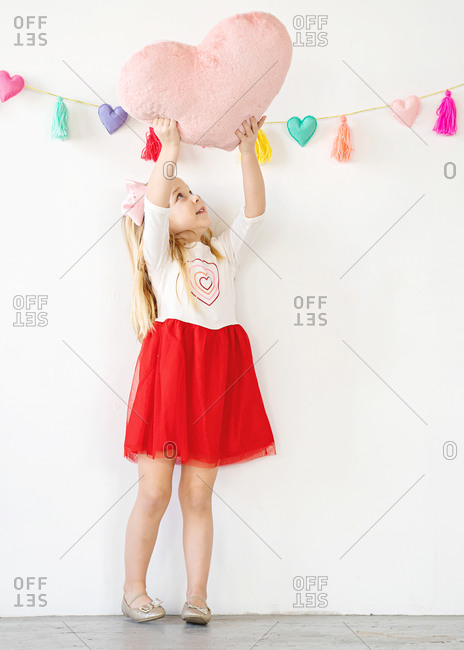 Cute young girl holding pink heart pillow up over head