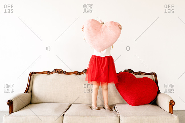Little girl holding big pink heart pillow on couch indoors